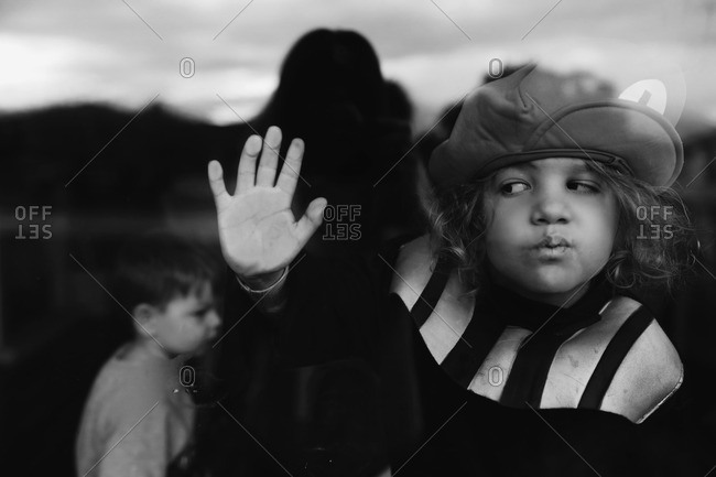 Boy pressing his face and hand against window glass