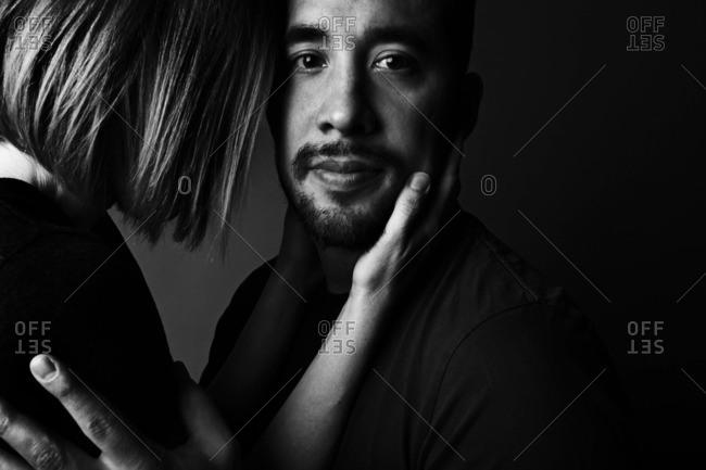 Man and woman standing face-to-face holding each other