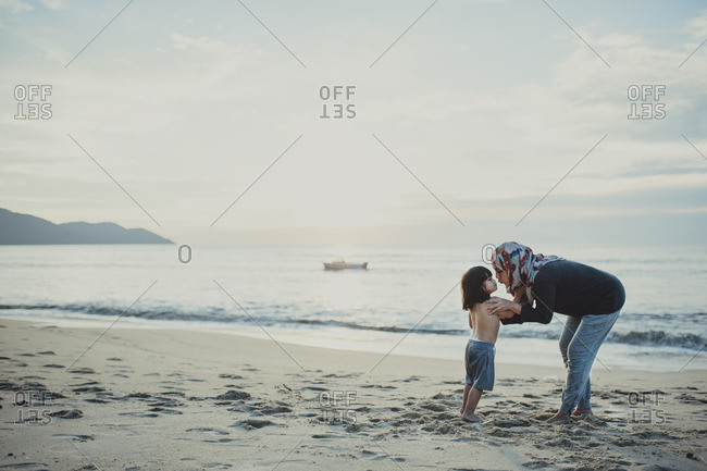 Mom kissing her son on beach