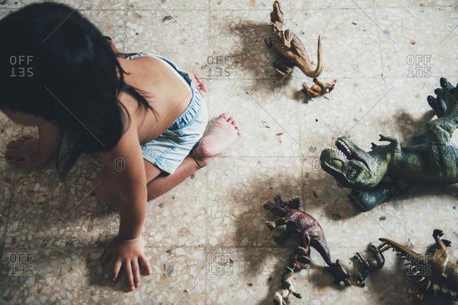 Boy crawling on floor by toys
