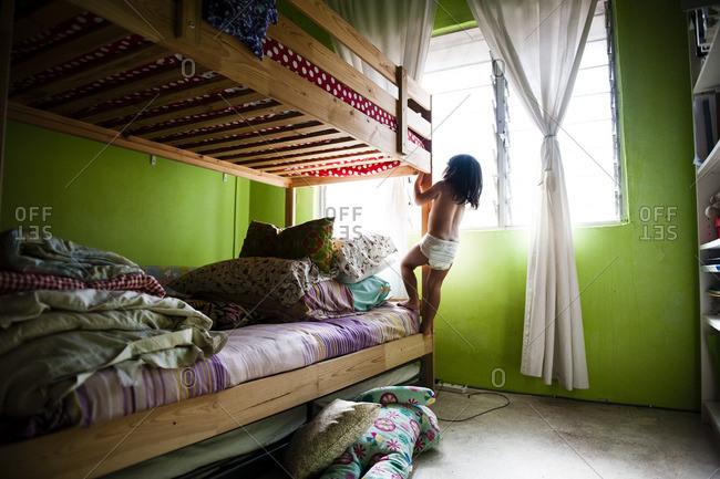 Boy in diaper climbing bunk bed
