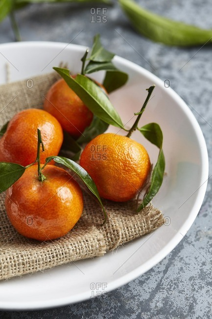Satsumas with leaves on a plate