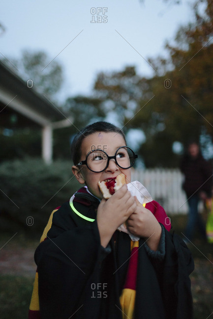 Boy in wizard costume eating hot dog