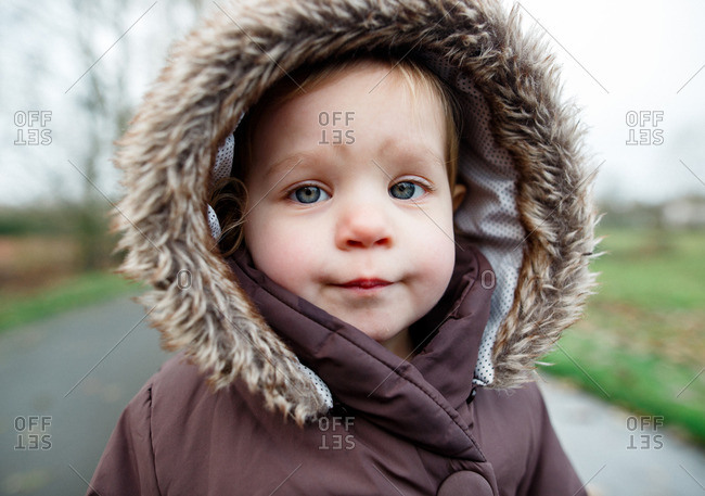 Toddler girl in fur lined hooded coat