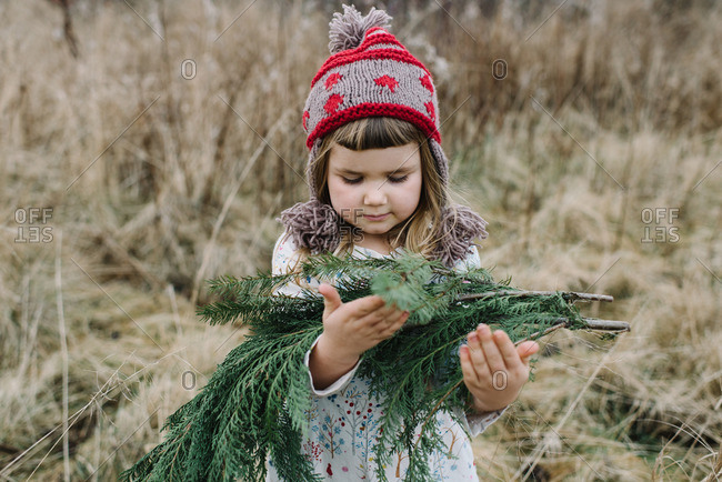 Little girl holding winter greenery