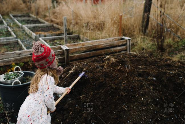 Girl shoveling dirt in garden