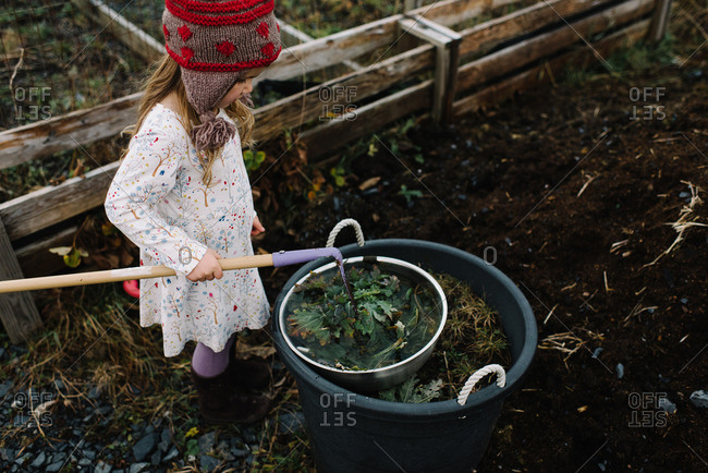Girl holding a garden hoe standing next to a large bucket full of weeds