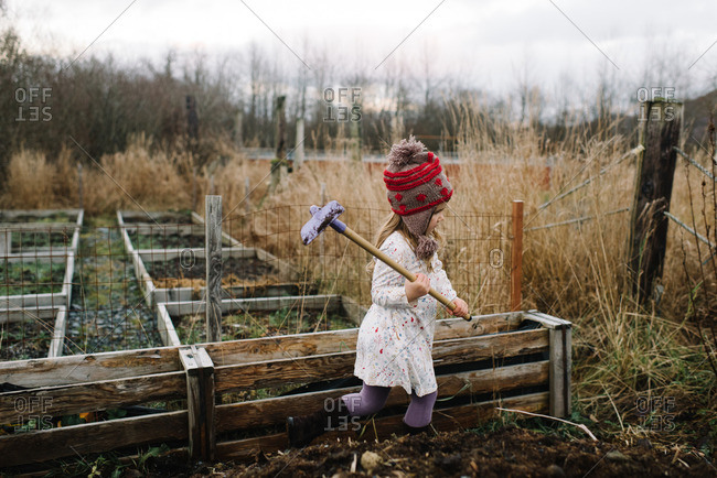 Girl holding a hoe over her shoulder walking through garden