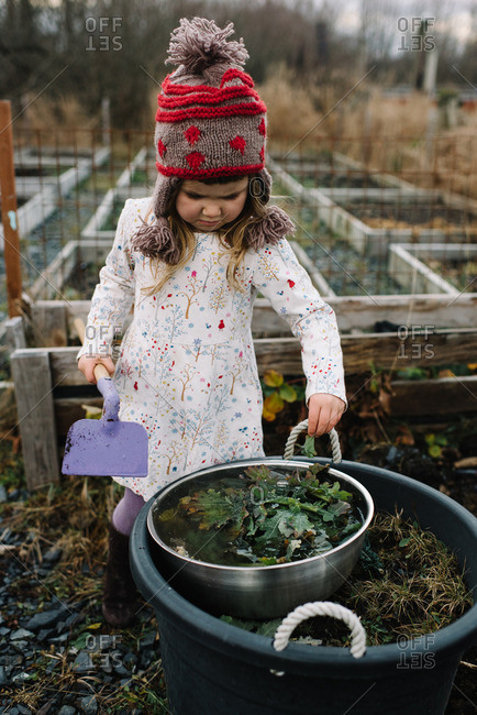 Girl holding a garden hoe looking at a large bucket full of leaves and vegetation