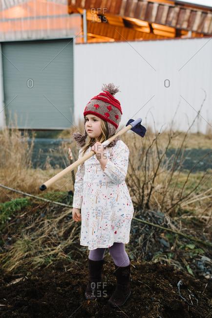 Girl holding a garden hoe over her shoulder