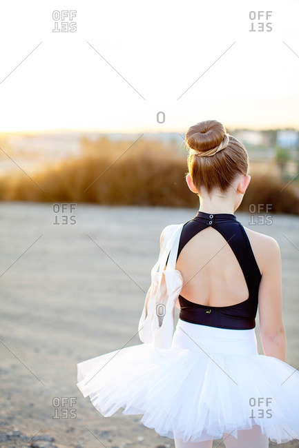 Girl walking outside in ballet outfit carrying her slippers