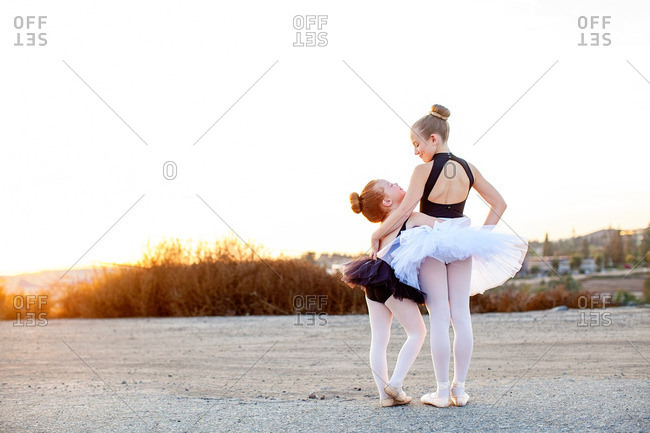 Two ballerinas hugging outdoors at sunset