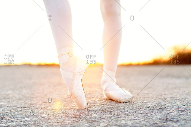 Close up of girl wearing ballet slippers at sunset