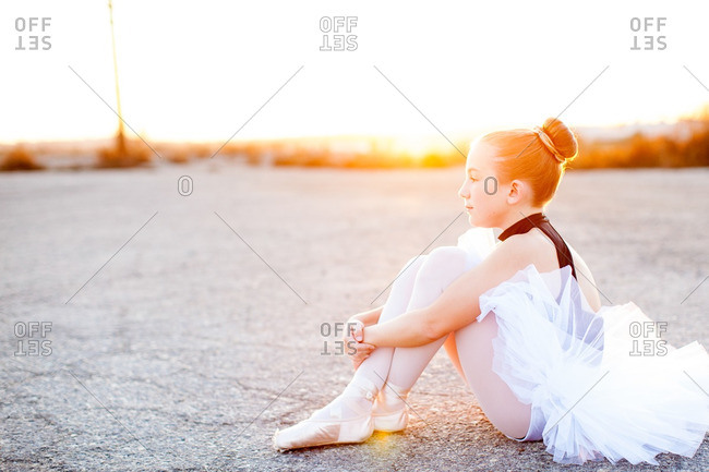 Girl in ballet costume sitting on the ground at sunset