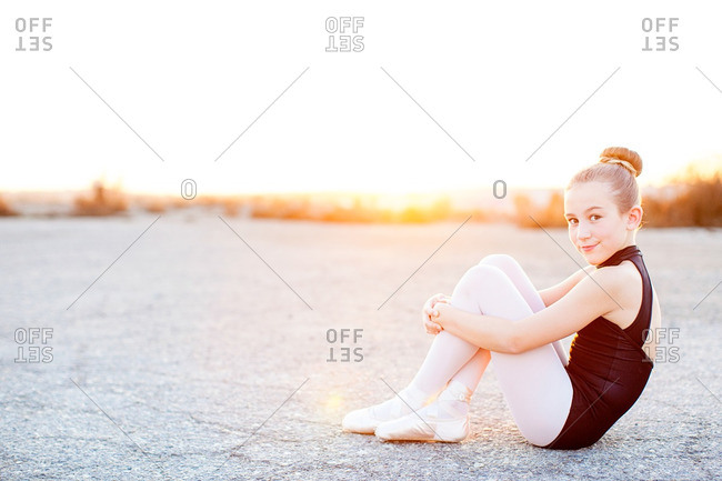 Ballerina sitting on the ground at sunset looking at camera