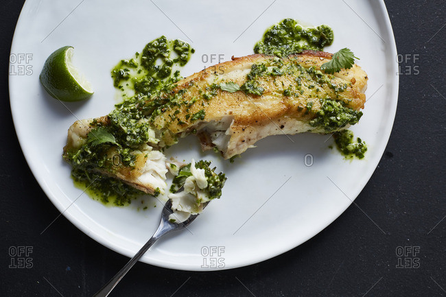 Roasted fish fillet on a plate topped with pesto