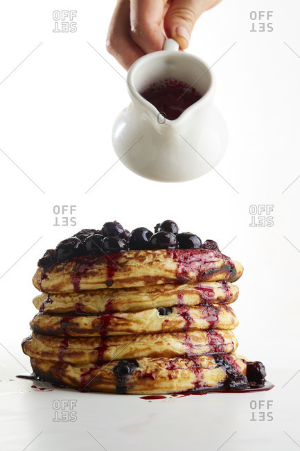 Hand pouring syrup over blueberry topped pancakes