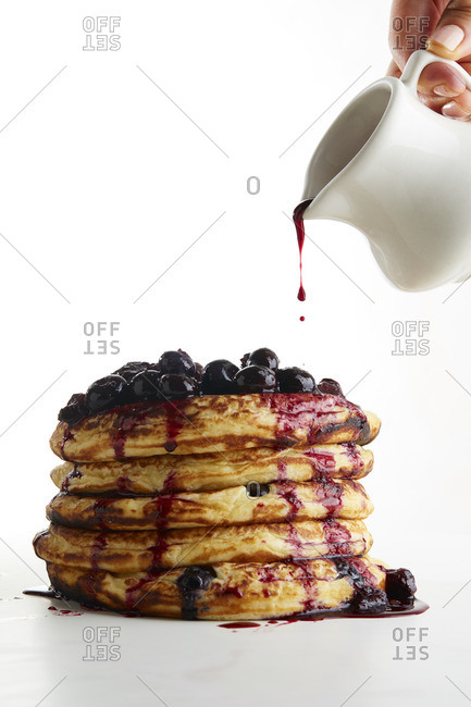 Hand pouring syrup over stack of blueberry topped pancakes