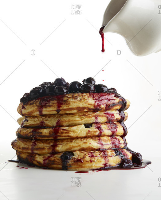 Syrup dripping over stack of blueberry topped pancakes