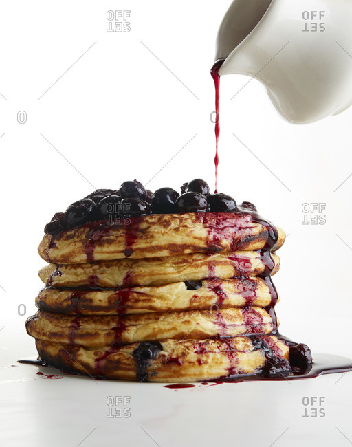 Syrup dripping over stack of pancakes with blueberries