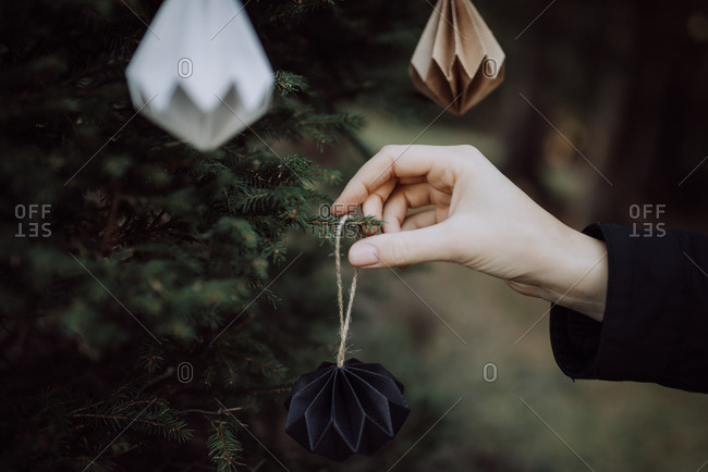 Person hanging a handmade paper ornament on Christmas tree