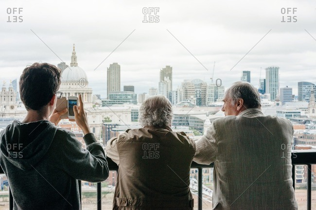 Three generations of men on a balcony overlooking London while taking photo on smartphone