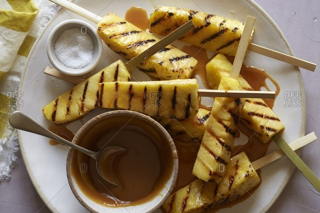 Grilled pineapple on bamboo sticks with caramel sauce