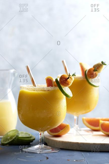 Orange tropical cocktails garnished with paper fruits