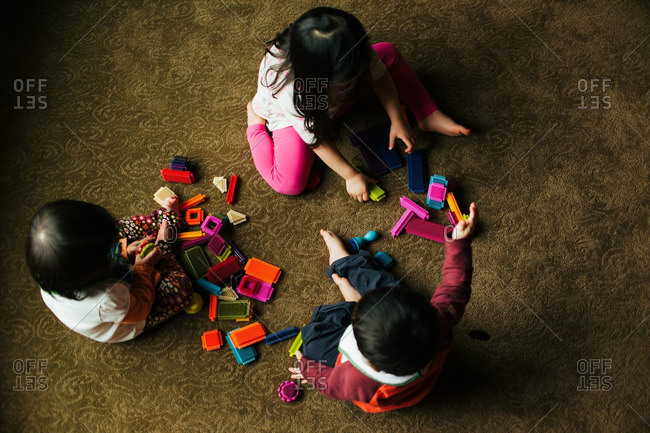 Three siblings playing with toys indoors
