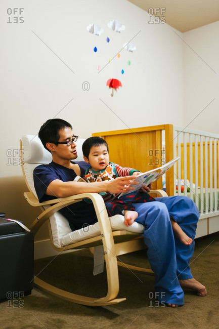 Father reading bedtime story to toddler son in a nursery