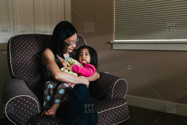 Mother cuddling with daughter in a comfy chair