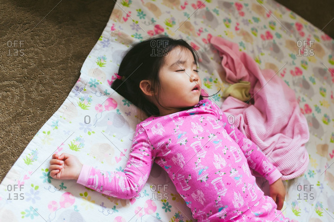 Little girl sleeping on a blanket on the floor