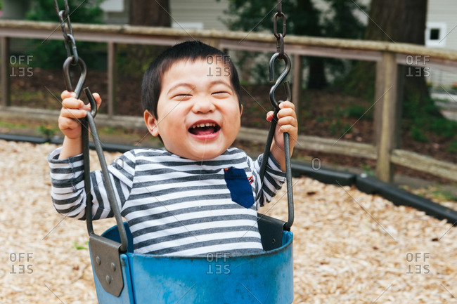 Happy baby boy swinging on a park swing
