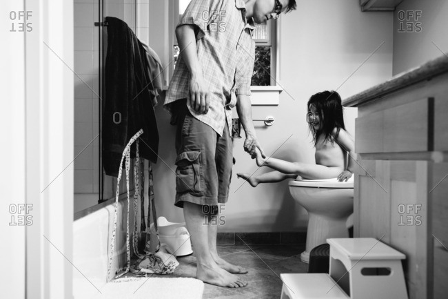 Father tickling daughters feet while she sits on the toilet