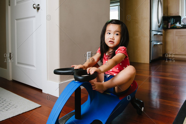 Little girl riding in house on a ride on toy