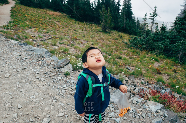 Little boy hiking on trail with backpack and bag of snacks