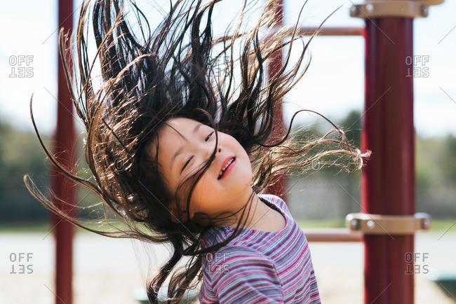 Girl swinging hair around at a park
