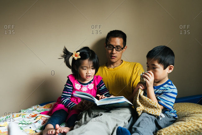 Father reading story to toddler twins