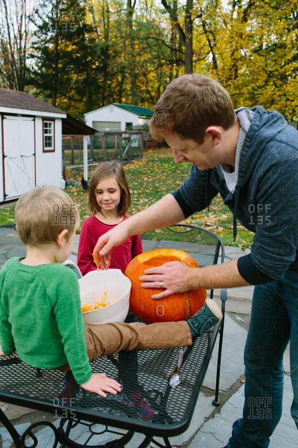 Father carving pumpkins with his children
