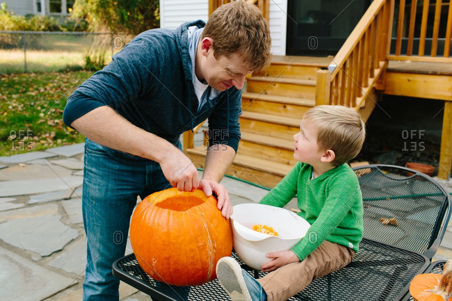 Father carving a pumpkin with his son