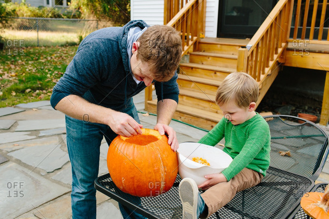 Father and son carving a pumpkin