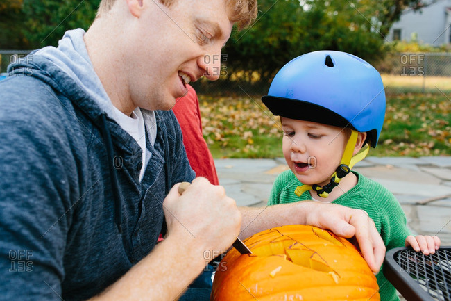 Father carving a jack-o-lantern with his son