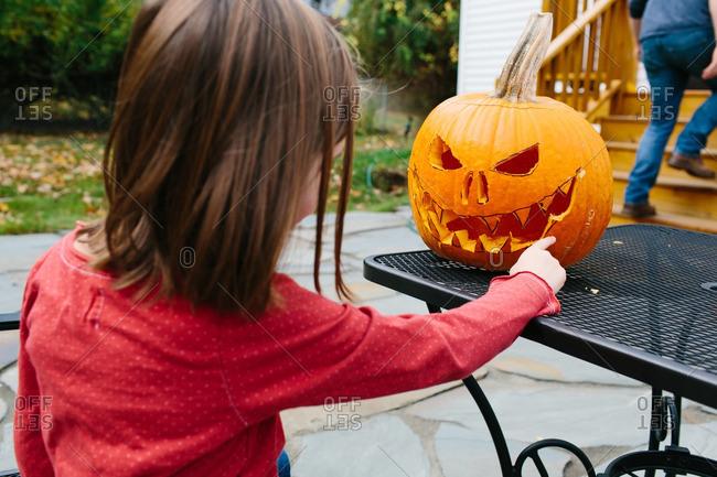 Little girl touching a freshly carved jack-o-lantern