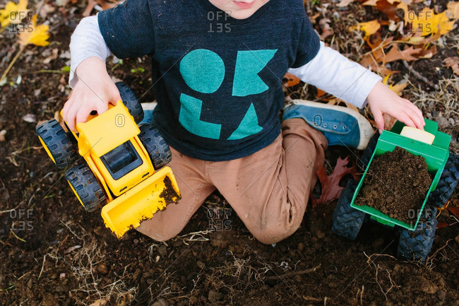 Little boy playing with toy trucks in the dirt and fallen leaves