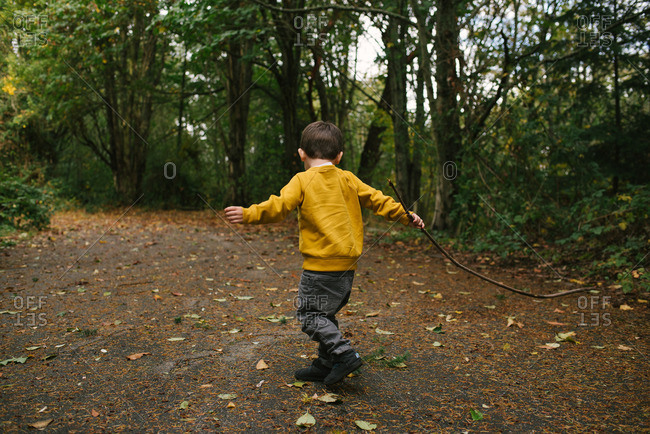 Boy walking on a nature trail with a stick