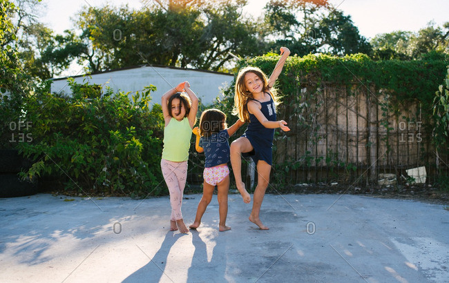 Three sisters dancing and playing in a driveway