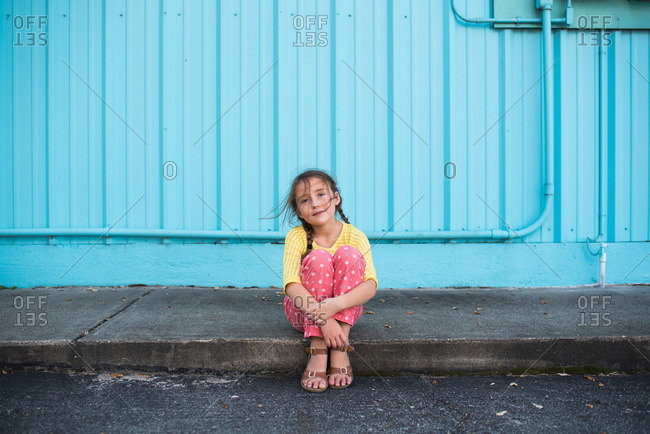 Little girl sitting on a curb beside a blue building