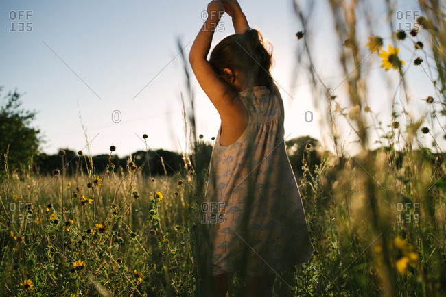 Girl playing in a field of wild flowers
