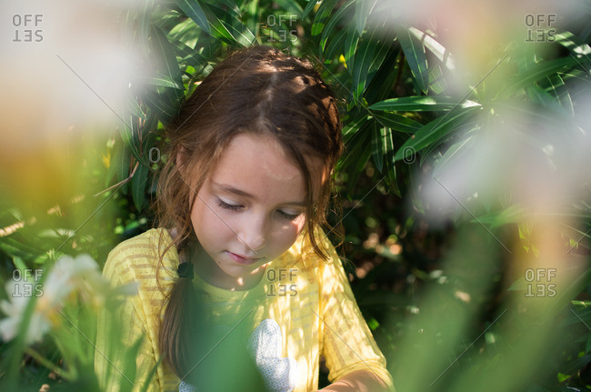 Little girl sitting in among flowers and tree branches