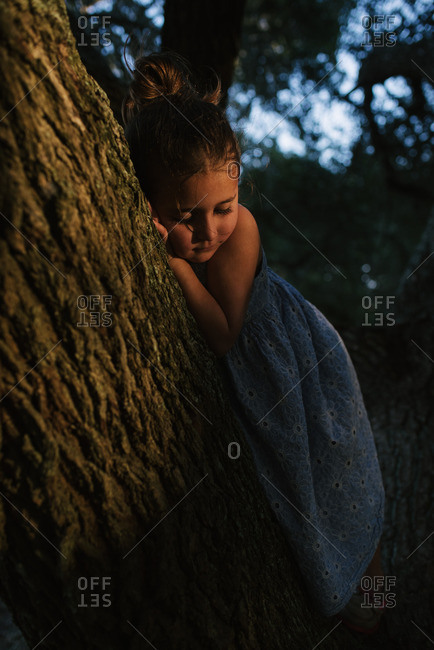 Little girl resting against a large tree branch